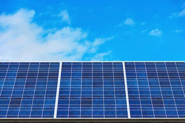 Blauwe zonnepanelen (zonnecel) met blauwe wolkenhemelachtergrond in zonnelandbouwbedrijf.