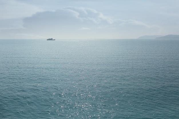 Blauwe zonnige zeewateroppervlakte met veerboot. de achtergrond van de de zomertijd.
