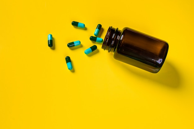Blauwgroene capsules gegoten uit een bruine transparante pot voor medicijnen op een gele achtergrond