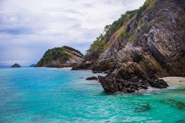 Blauwgroene oceaan met rotsberg vol wolkendag. zeezicht en natuurlijke achtergrond.