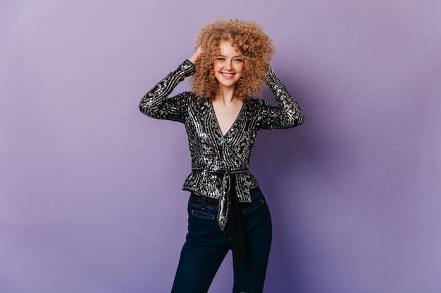 Blauwogig glimlachend meisje raakt haar blonde krullen aan. vrouw in donkere jeans en glanzend shirt met ornament.