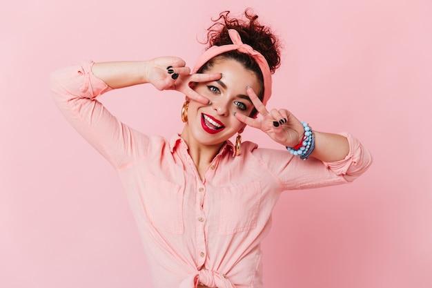 Blauwogig meisje met rode lippenstift vertoont tekenen van vrede. vrouw in hoofdband en met armbanden aan haar arm glimlacht op roze ruimte.