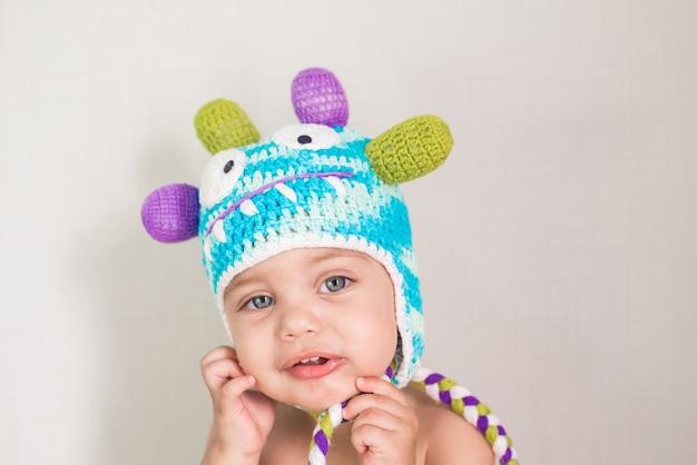 Blauwogige babyjongen op witte achtergrond met klein monster glb op hoofd - grappig gezicht