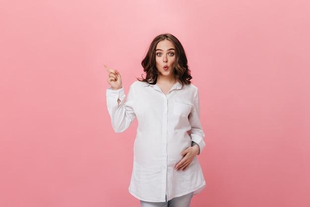 Blauwogige brunette zwangere vrouw in wit overhemd en denim broek fluit en wijst op plaats voor tekst op geïsoleerde roze achtergrond.