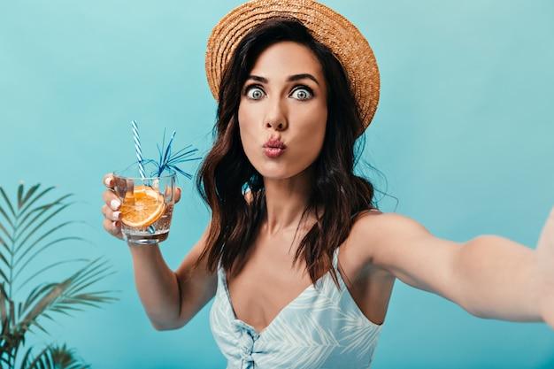 Blauwogige dame fluit, neemt selfie en houdt glas water met sinaasappel vast