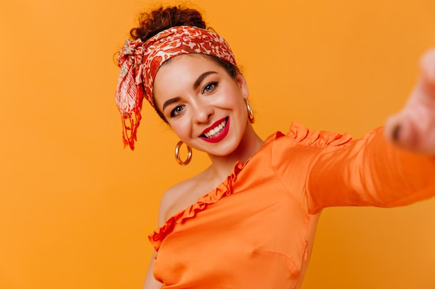 Blauwogige dame met rode lippen neemt selfie op oranje ruimte. portret van meisje in enorme oorbellen, oranje sjaal op haar hoofd en blouse.
