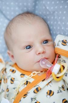 Blauwogige pasgeboren baby met een fopspeen ligt en kijkt. gelukkige jeugd. ouderlijke zorg.