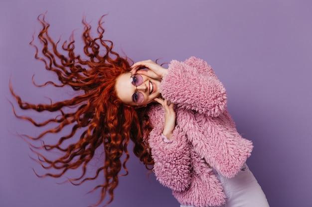 Blauwogige vrouw in lila glazen danst en speelt met haar haar. foto van meisje in roze jas op geïsoleerde ruimte.