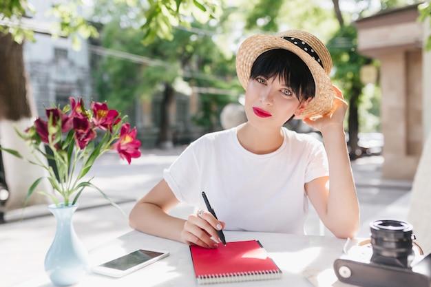 Blauwogige vrouwelijke student in strooien hoed huiswerk op terras, zittend met pen en notitieblok