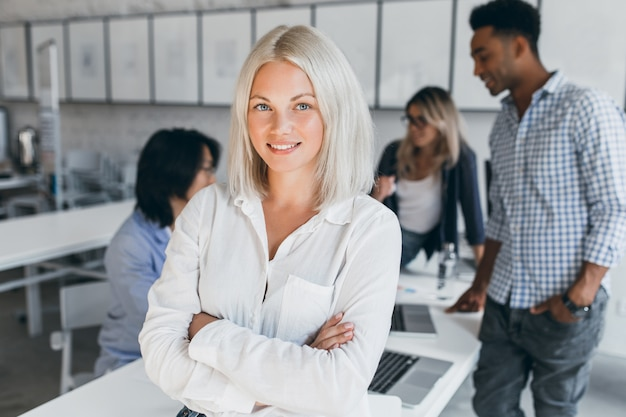 Blauwogige zakenvrouw in witte blouse staande in vertrouwen pose met haar internationale medewerkers. indoor portret van aziatische en afrikaanse werknemers met blonde dame.