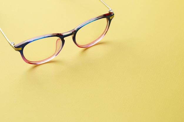 Blauwroze bril op gele ruimte