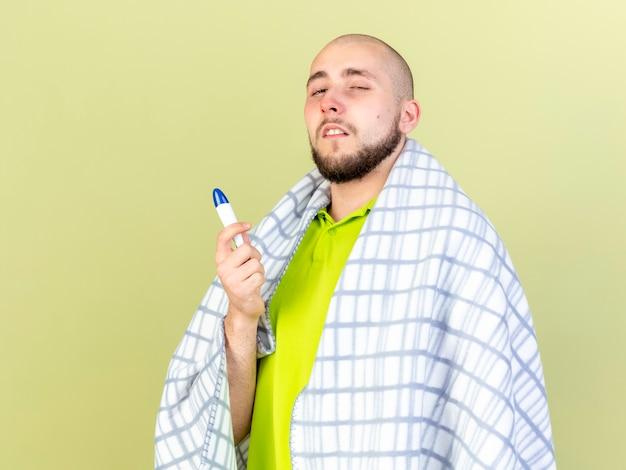 Bleke jonge blanke zieke man gewikkeld in plaid houdt thermometer op olijfgroen