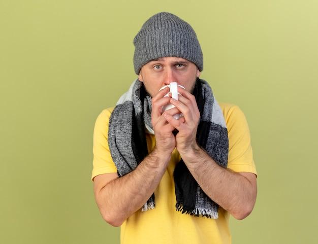 Bleke jonge blonde zieke slavische man met muts en sjaal drinkt kopje thee geïsoleerd op olijfgroene muur met kopie ruimte