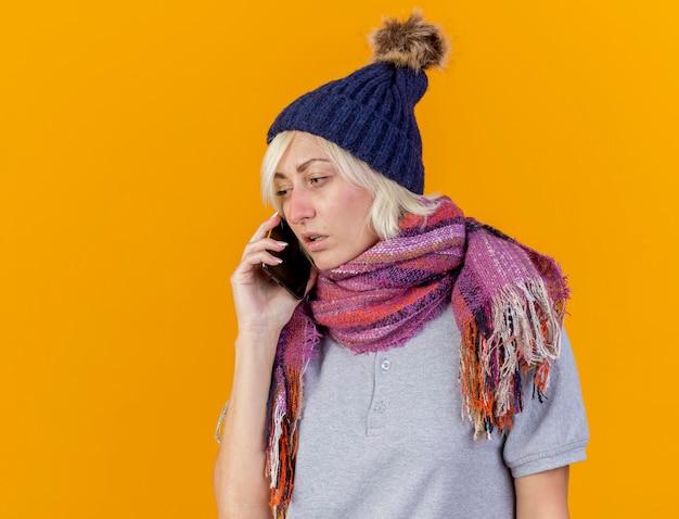 Bleke jonge blonde zieke slavische vrouw met winter hoed en sjaal praat over telefoon geïsoleerd op oranje