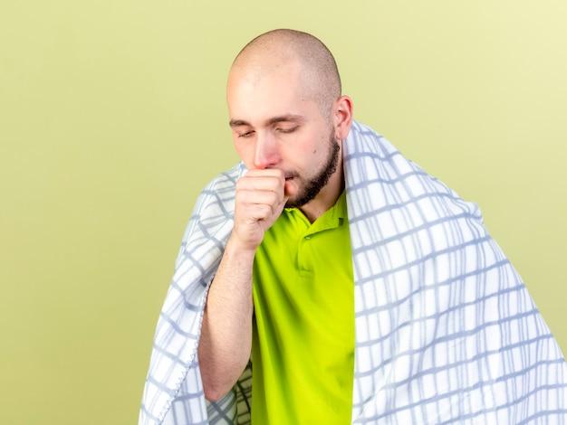 Bleke jonge zieke man gehuld in plaid hoesten geïsoleerd op olijfgroene muur