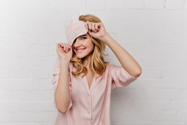 Bleke lachend meisje met krullend haar speels poseren op een witte muur. huiveringwekkende vrouw in oogmasker en zijden pyjama die thuis lachen.