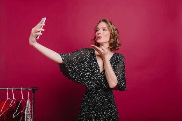 Bleke schattige vrouw lucht kus verzenden terwijl poseren in de kleedkamer