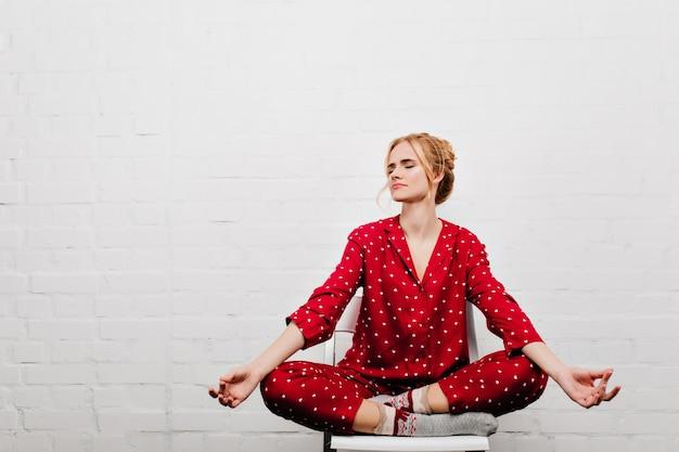 Bleke zalige meisje doet yoga op een witte muur. charmante blonde vrouw in rode nachtkostuum ontspannen voor het slapen.