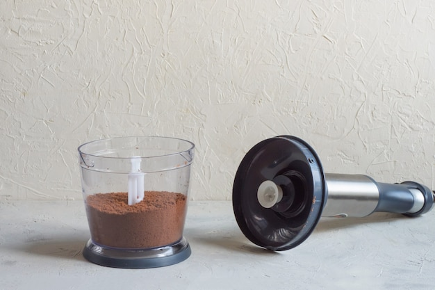 Blender op de keukentafel. proces van het malen van cacaobonen in een blender.