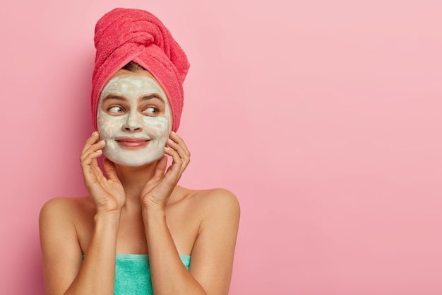 Blij, aangenaam uitziend vrouwelijk model heeft gezichtsmasker voor vochtige huid, toont schoon, fris gezicht, halfnaakt lichaam gewikkeld in handdoek, kijkt opzij op kopie ruimte