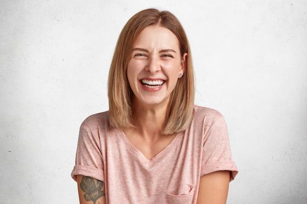 Blij aangenaam uitziende vrouw met oprechte brede glimlach lacht vrolijk naar de camera, luistert naar anekdotes, geïsoleerd over wit