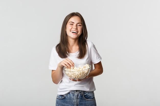 Blij aantrekkelijk donkerbruin meisje dat om komediefilm lacht, popcorn eet.