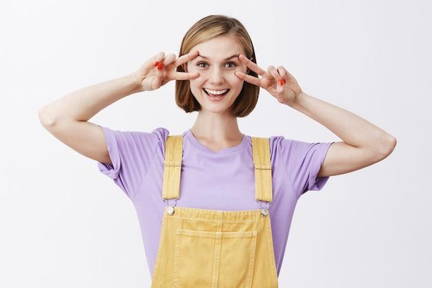 Blij aantrekkelijk kaukasisch meisje dat vredestekens over ogen maakt en vreugdevol glimlacht