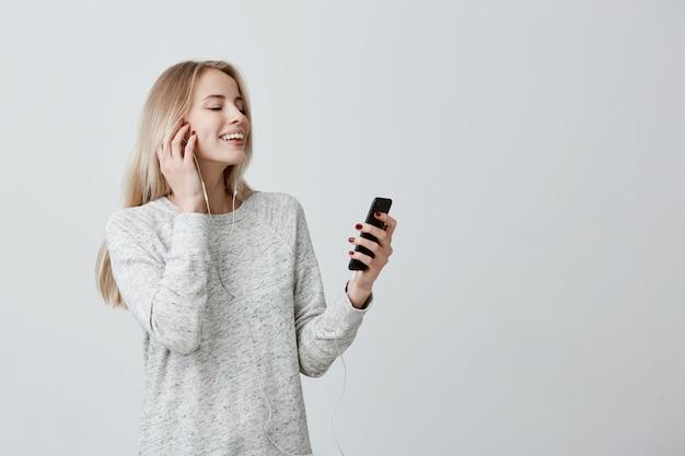 Blij aantrekkelijk vrouwtje met blond geverfd haar dat binnenshuis staat met haar smartphone te chatten