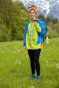 Blij actieve toerist poseert op groen gras tegen bergen en bos, bewondert prachtige natuur