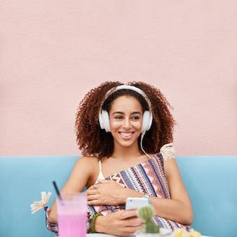 Blij afrikaans-amerikaans vrouwelijk model geniet van favoriete afspeellijst, meloman zijn