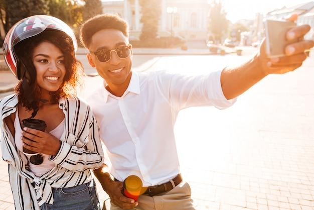 Blij afrikaans paar dat selfie op smartphone maakt terwijl ze op straat is