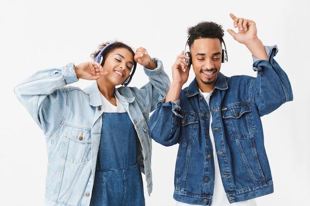 Blij afrikaans paar in denim shirts luisteren muziek door koptelefoon en dansen samen over grijze muur