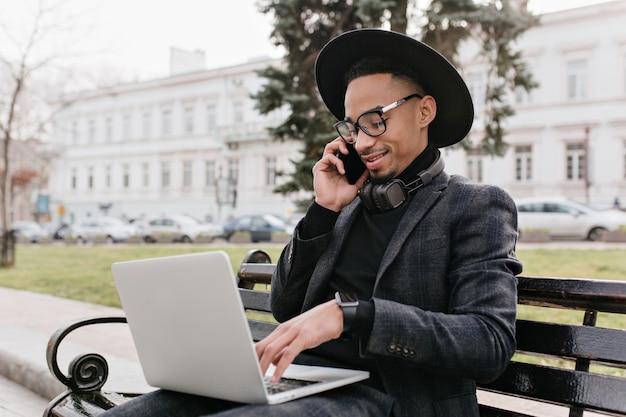 Blij afrikaanse freelancer praten over de telefoon en typen op toetsenbord. buitenfoto van internationale student in zwarte outfit met laptop op aard.