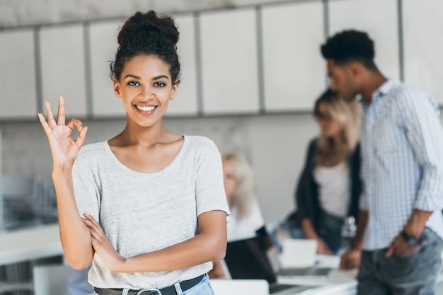 Blij afrikaanse kantoormedewerker met lichtbruine huid die goed teken toont na conferentie met buitenlandse partners. portret van vrouwelijke zwarte freelancer die van succesvol project geniet.