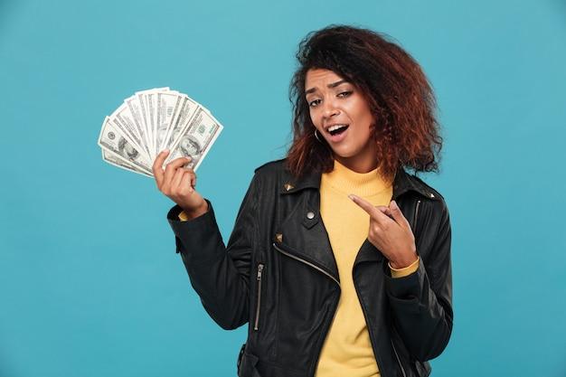 Blij afrikaanse vrouw in lederen jas aanhouden van geld