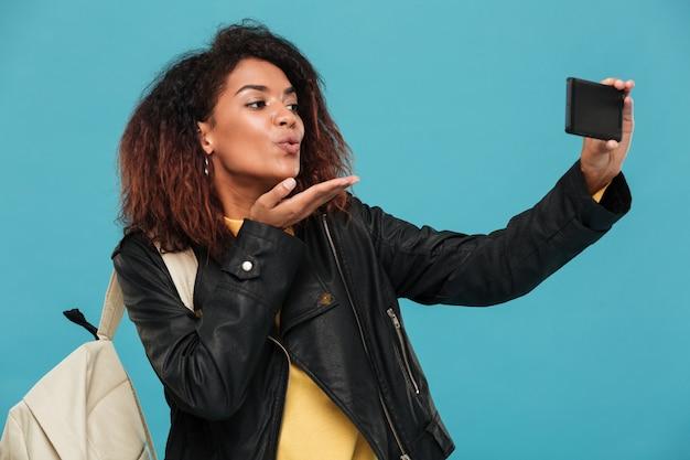 Blij afrikaanse vrouw in leren jas met rugzak selfie maken