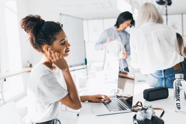 Blij afrikaanse vrouwelijke manager ontspannen met de ogen gesloten in koptelefoon tijdens koffiepauze. indoor portret van jonge kantoorpersoneel van internationaal bedrijf rusten na een zware dag.