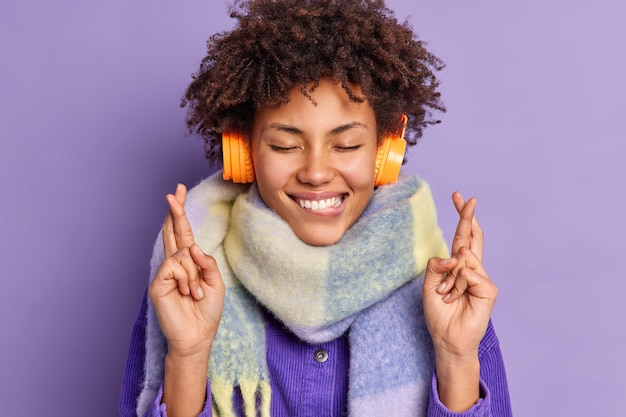 Blij afro-amerikaanse tienermeisje houdt ogen gesloten bijt lippen staat bijgelovig kruist vingers voor geluk draagt koptelefoon op oren sjaal om nek
