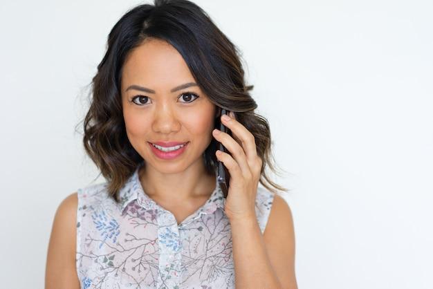 Blij aziatisch meisje dat op telefoon spreekt