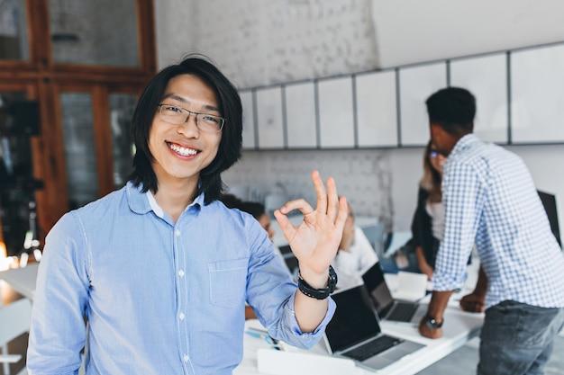 Blij aziatische man in klassiek blauw t-shirt poseren met goed teken na conferentie met collega's. binnenportret van gelukkige chinese ondernemer in glazen die van goede dag genieten.