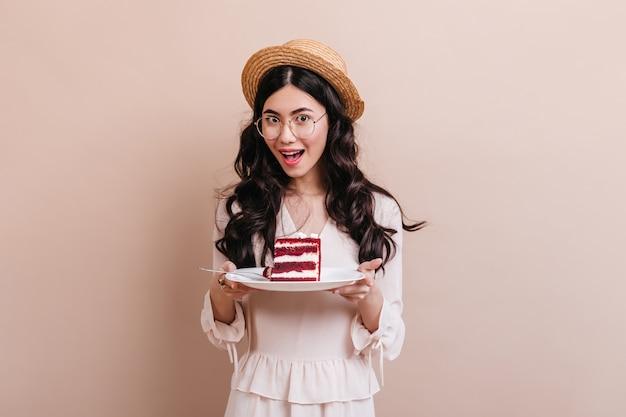 Blij aziatische vrouw met plaat met cake. studio die van chinese vrouw in strohoed is ontsproten.