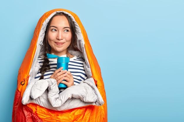 Blij aziatische vrouwelijke toerist houdt kolf met warme drank, gewikkeld in een warme slaapzak, brengt de nacht door in de open lucht, heeft tevreden uitdrukking, natuurlijke schoonheid geïsoleerd op blauwe muur