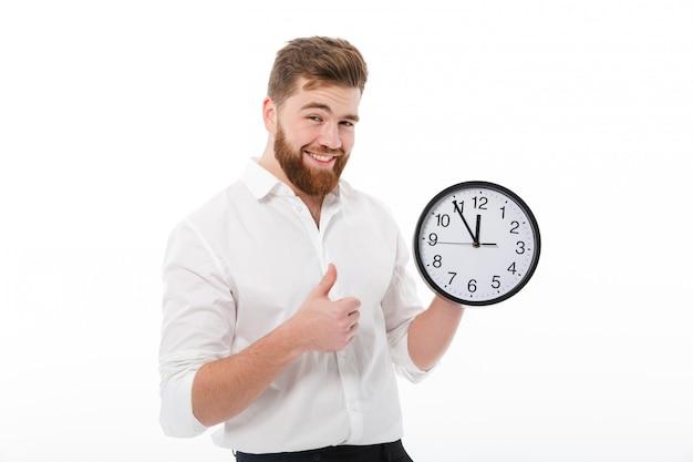 Blij bebaarde man in zakelijke kleding bedrijf klok