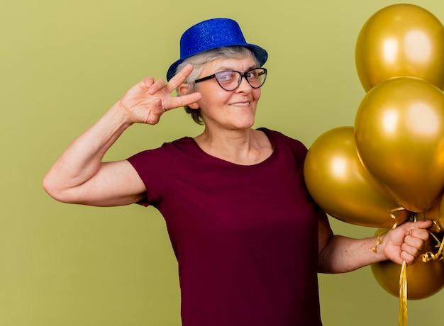 Blij bejaarde vrouw in optische bril met feestmuts staat met helium ballonnen overwinning gebaren