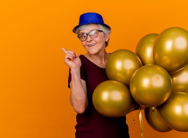 Blij bejaarde vrouw in optische bril met feestmuts staat met helium ballonnen wijzend naar kant geïsoleerd op oranje muur