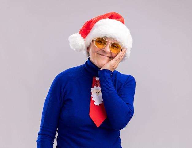 Blij bejaarde vrouw in zonnebril met kerstmuts en kerststropdas legt hand op gezicht