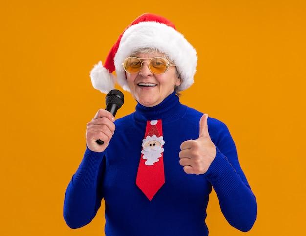 Blij bejaarde vrouw in zonnebril met kerstmuts en santa stropdas houdt microfoon en duimen omhoog geïsoleerd op oranje muur met kopie ruimte