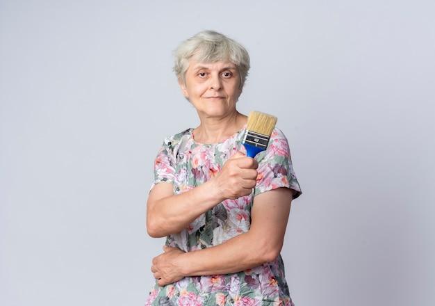 Blij bejaarde vrouw legt hand op buik houdt kwast geïsoleerd op een witte muur