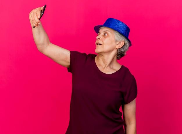 Blij bejaarde vrouw met feestmuts houdt en kijkt naar de telefoon op roze