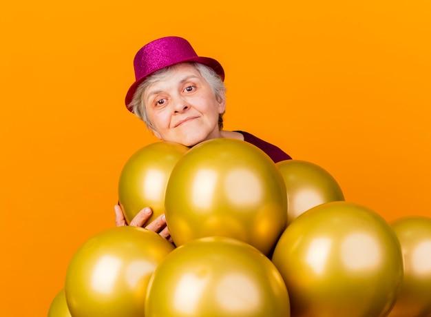 Blij bejaarde vrouw met feestmuts houdt en staat met helium ballonnen op oranje